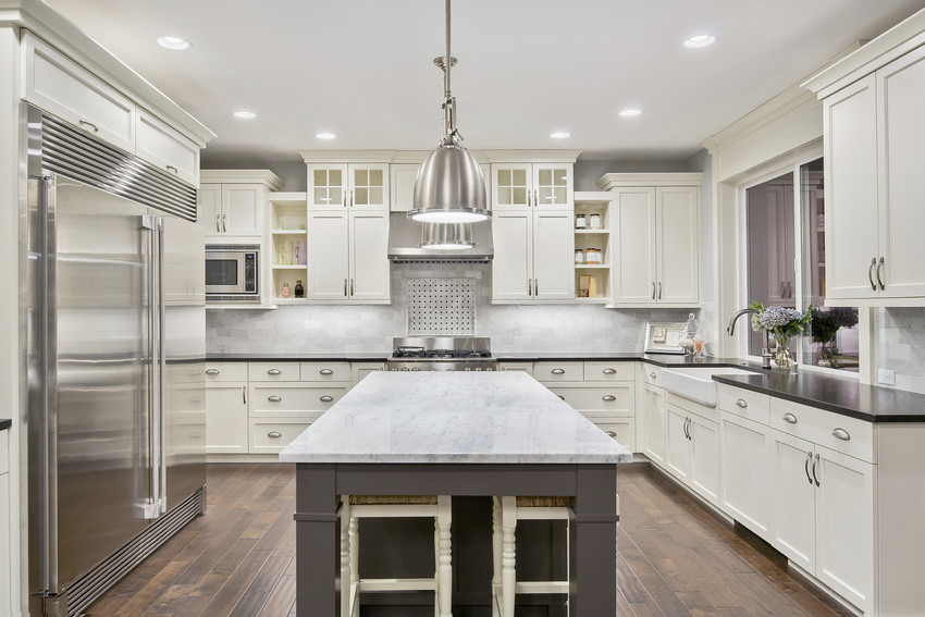 High-end kitchen with marble countertops and silver fridge.