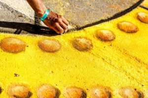 Woman drawing with yellow chalk on the street.